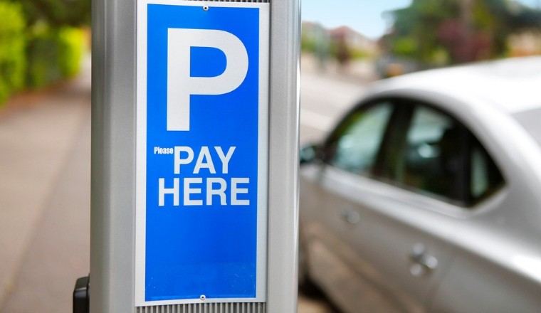 """A silver car next to a parking metre that has a sign """"pay here"""""""