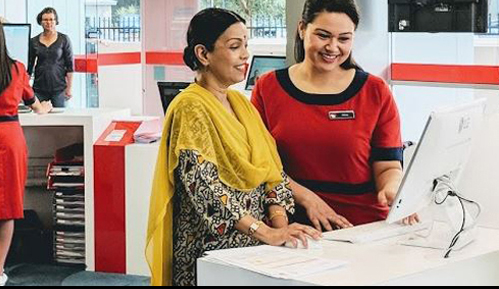 Happy customer being guided through a transaction by a Service NSW employee