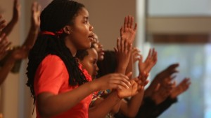 A young African-American woman sings with a choir