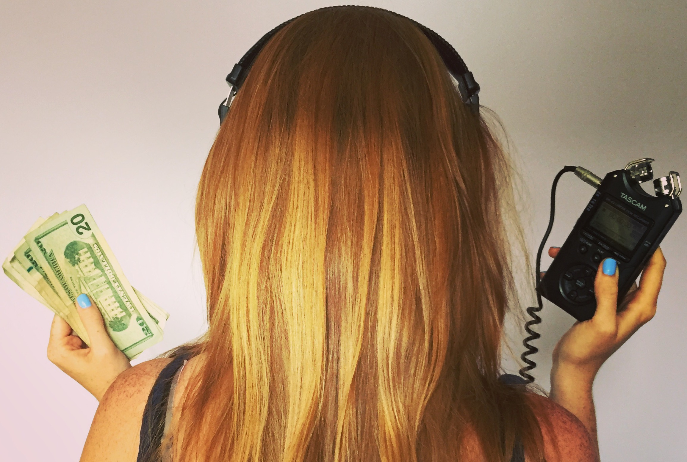 A woman with red hair and headphones is seen from the back holding a fistful of $20 bills in her left hand, and an audio recorder in her right