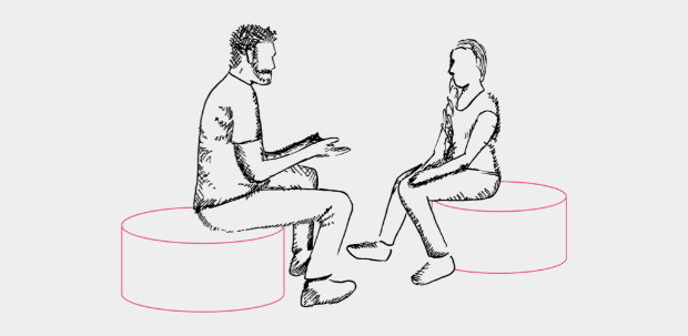 Man and woman sitting down having a discussion.