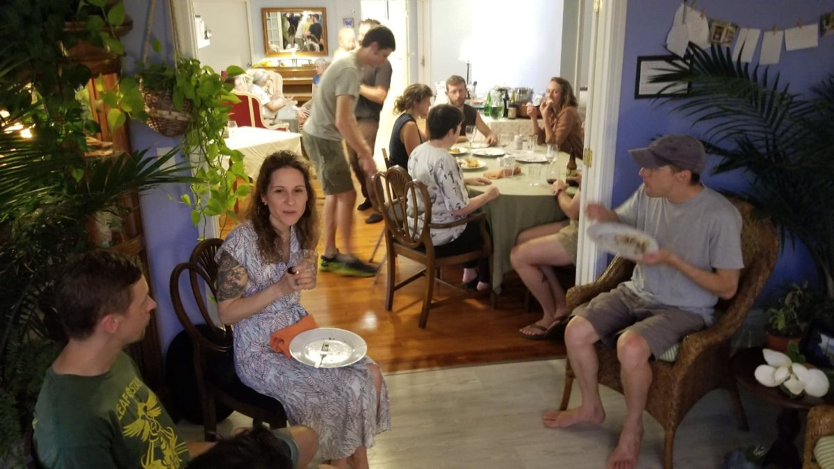 People at the last potluck seated around, some holding plates.