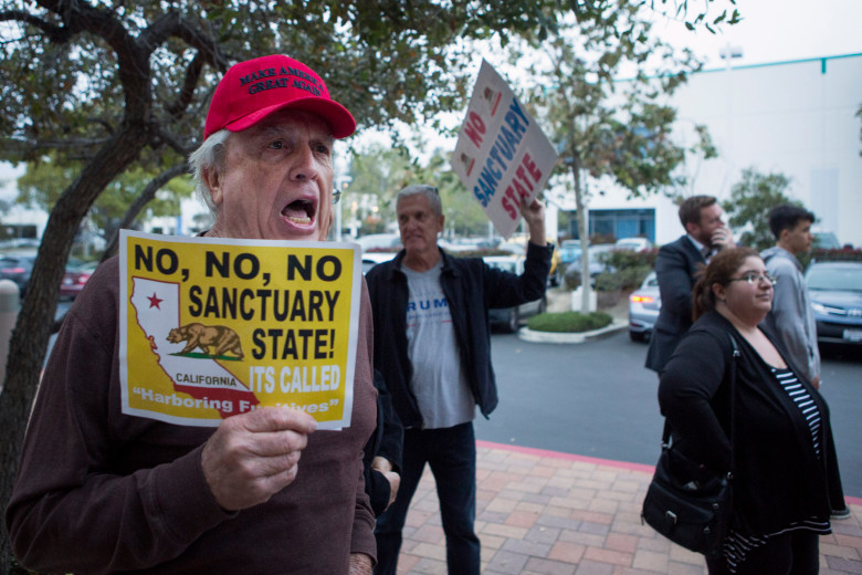"""Vaughn Becht of Westminster chants, """"Build that wall, build that wall!"""" outside Aliso Viejo City Hall during a meeting discussing whether or not the city should file a friend-of-the-court brief in support of the City of Los Alamitos and also the Orange County Board of Supervisors in United States V. State of California on Wednesday, April 4, 2018. (Photo by Drew A. Kelley, Contributing Photographer)"""