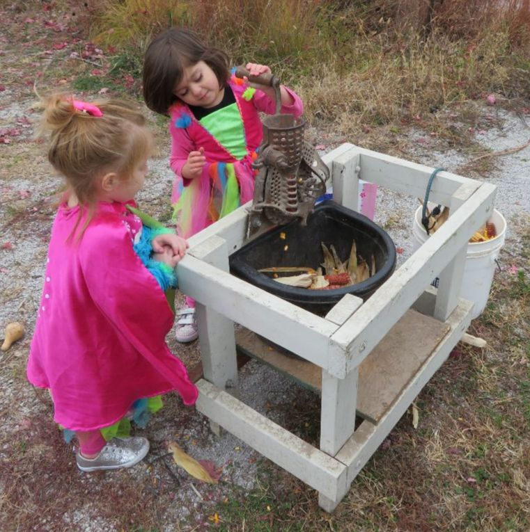Two young princess fairies work the corn grinder with curiosity