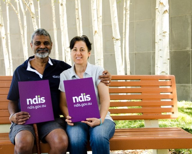 Image of a man and a woman sitting on a park bench. The man has his arm around the woman and both are looking at the camera smiling. They are holding purple signs that read 'NDIS ndis.gov.au'