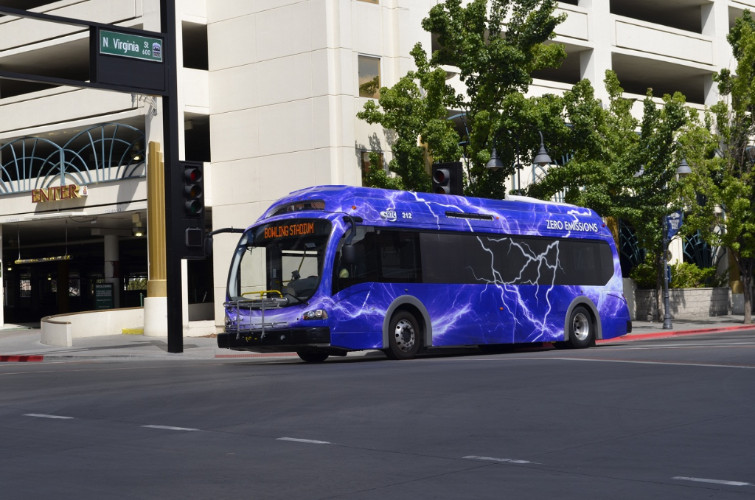 A blue electric bus in downtown