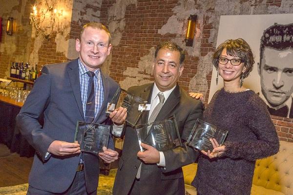 Communications staff holding awards