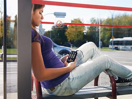 Meisje luisterleest wachtend op de bus