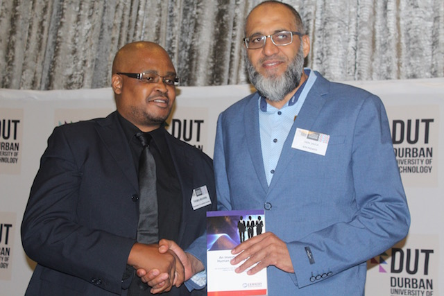 Dr Themba Msukwini handing over his book to Faizal Salfa