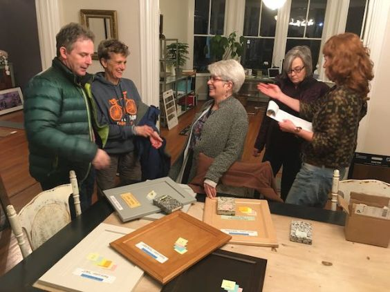 people with a table of wood colors and samples