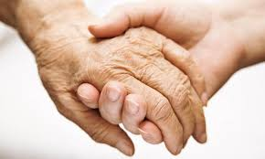 older adults hand placed in hand of younger person