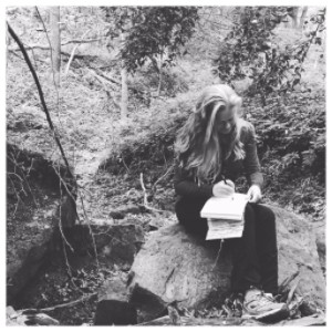 Picture of Gena Foster journaling in the woods