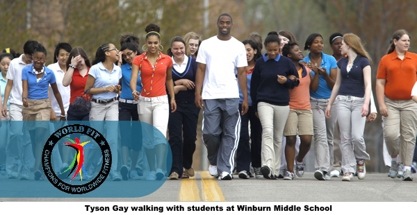 Olympian walking with World Fit Students
