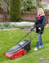 photo of woman mowing her lawn with an electric lawnmower