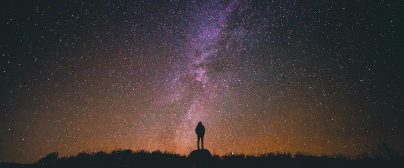 Silhouette of a human figure against a vast starry sky.