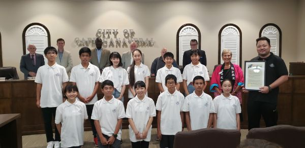 Group of international students stand with City Council members