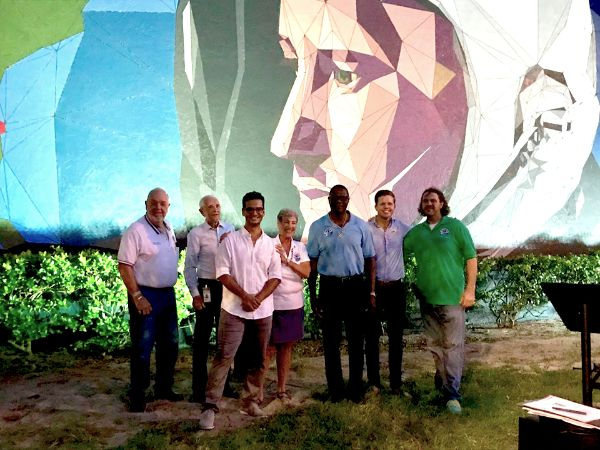 group of people in front of space mural