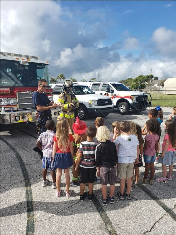 2 firefighters talk to group of small children