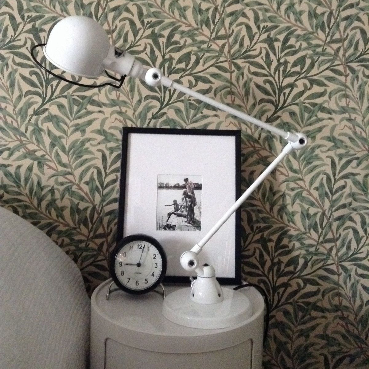 Lamp on bedside table with bold wallpaper
