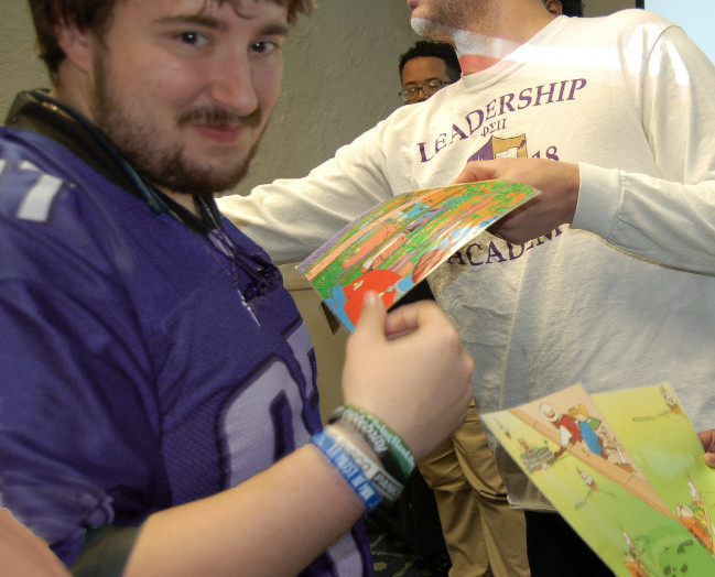 Young man holds large card with colorful design handed to him from another man with the word