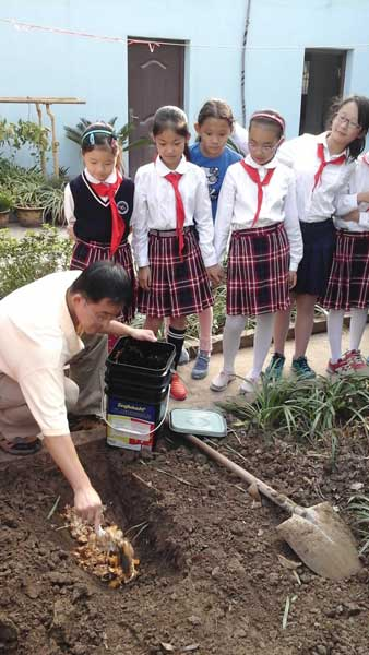 show students receiving instruction in burial of Bokashi fermented waste.