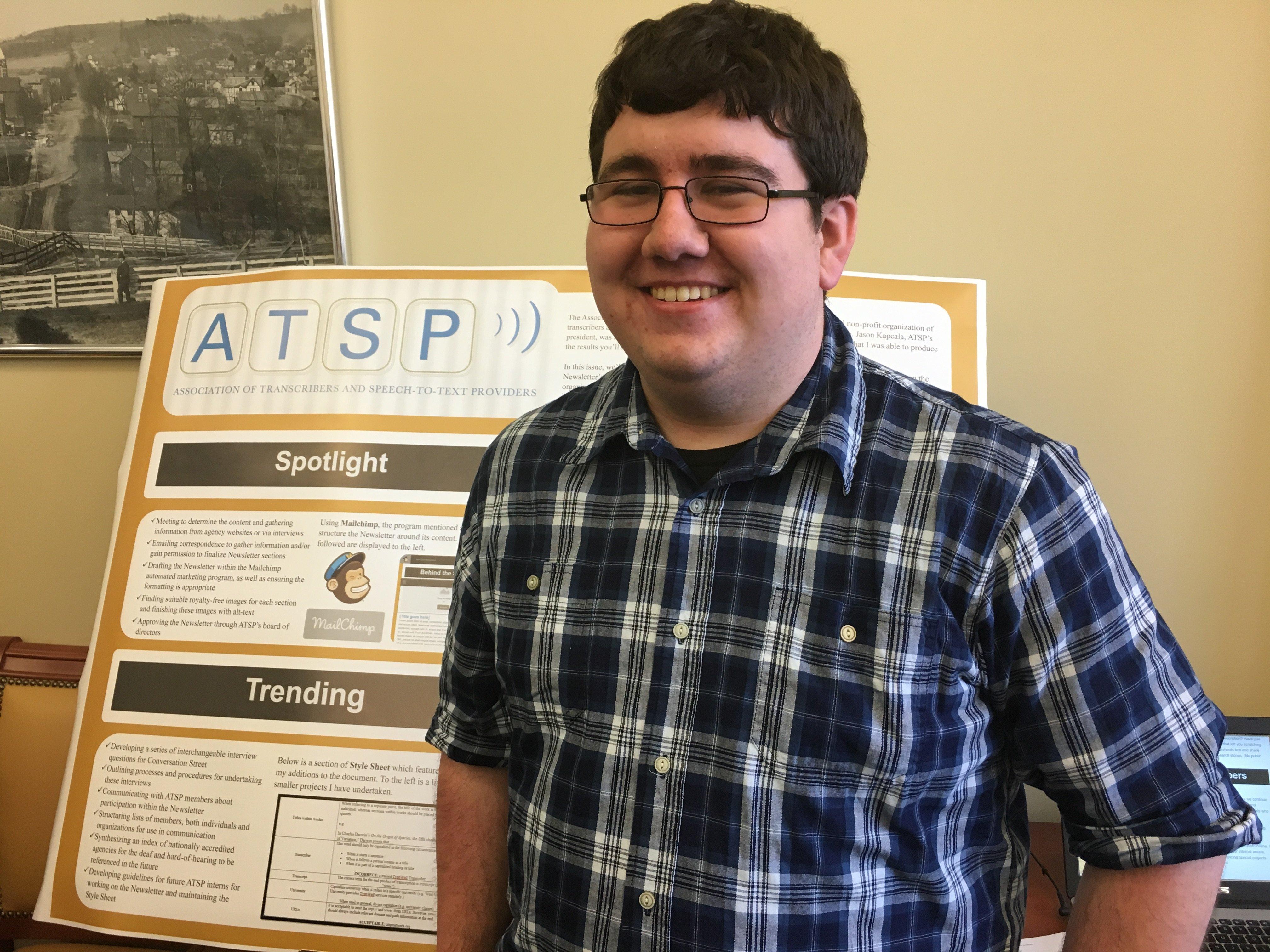 Intern Kody Goff standing in front of his internship poster presentation
