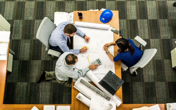 A group of professionals, possibly architects, workshop plans for an upcoming project while huddled over a large table.