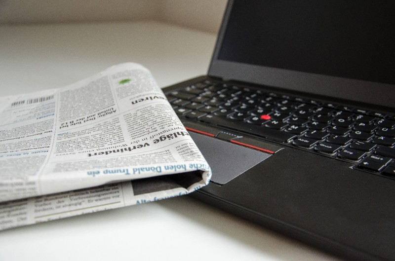 A newspaper sits roughly folded on a laptop, as if the user is undergoing an intensive job search