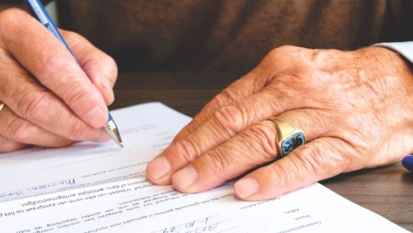 An old man with a ring signing a document