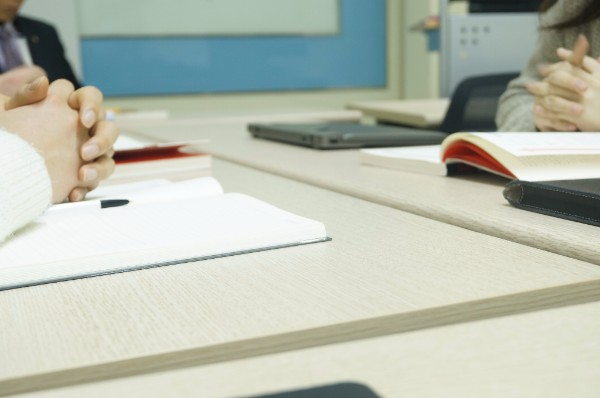 An image of a board meeting. Two people sit across from each other with their hands folded on top of notebooks. A man in a suit sits at the far end of the table