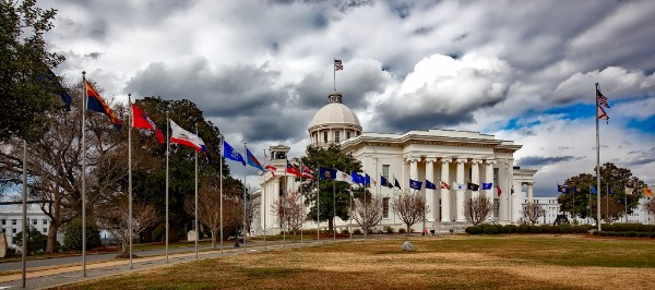 A photo of a state capitol, with many flags flying in front of the building