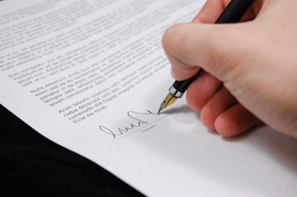 A person signing a contract using a fountain pen