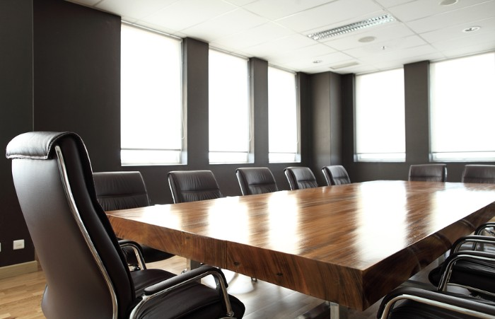 An empty board room with leather chairs surrounding a long table.