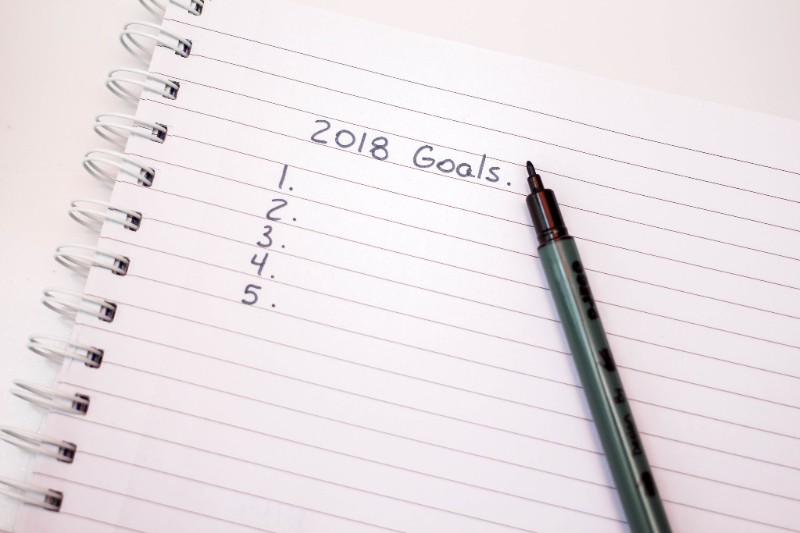 "A piece of notebook paper with a pen lying on it and the words ""2018 Goals"" above a blank list of five items."