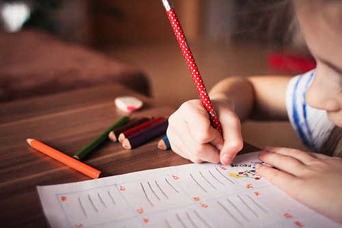 A young girl filling out a school worksheet