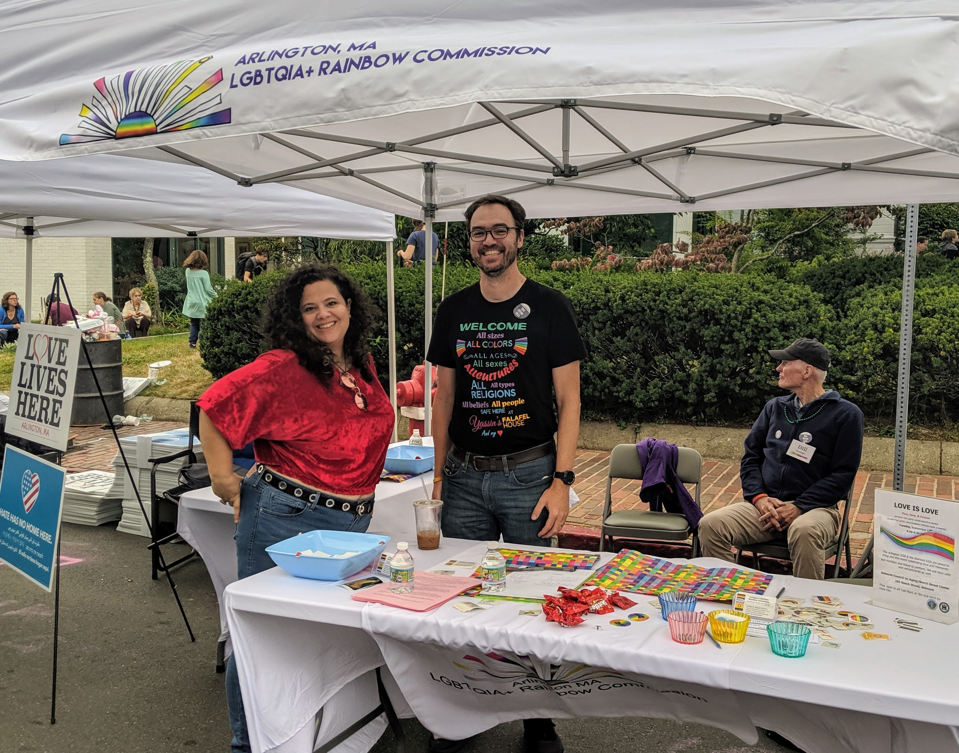 Volunteers and Commissioner Bill Gardiner at the Rainbow Commission's Town Day booth, with a table of Skittles, rainbow stickers, unicorn temp tattoos, and other giveaways