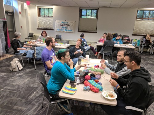 People gathered in the Community Room at the Robbins Library enjoying food, coloring, and learning to crochet
