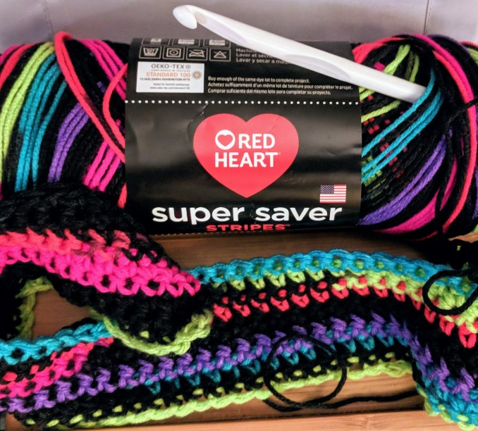 A colorful skein of variegated black and neon yarn, a white plastic crochet hook, and a few rows of single-crochet blanket