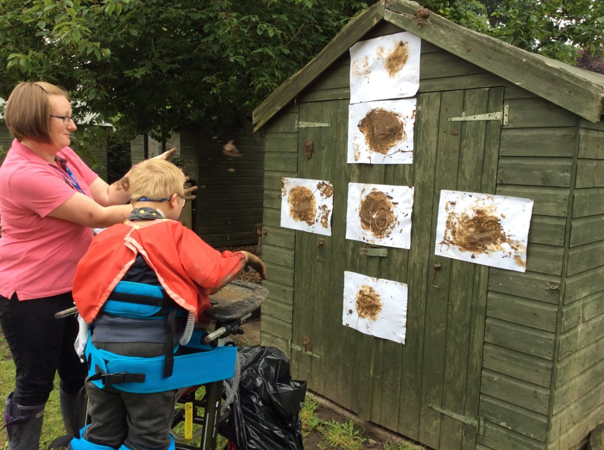 shed with mud splats all over it, with a teacher and child using a mobility aid to stand and throw mud