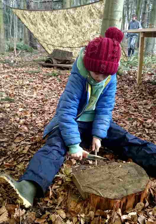 image-of-child-in-blue-outdoor-gear-and-red-bobble-hat-sat-on-a-log-whittling-a-stick-in-woods