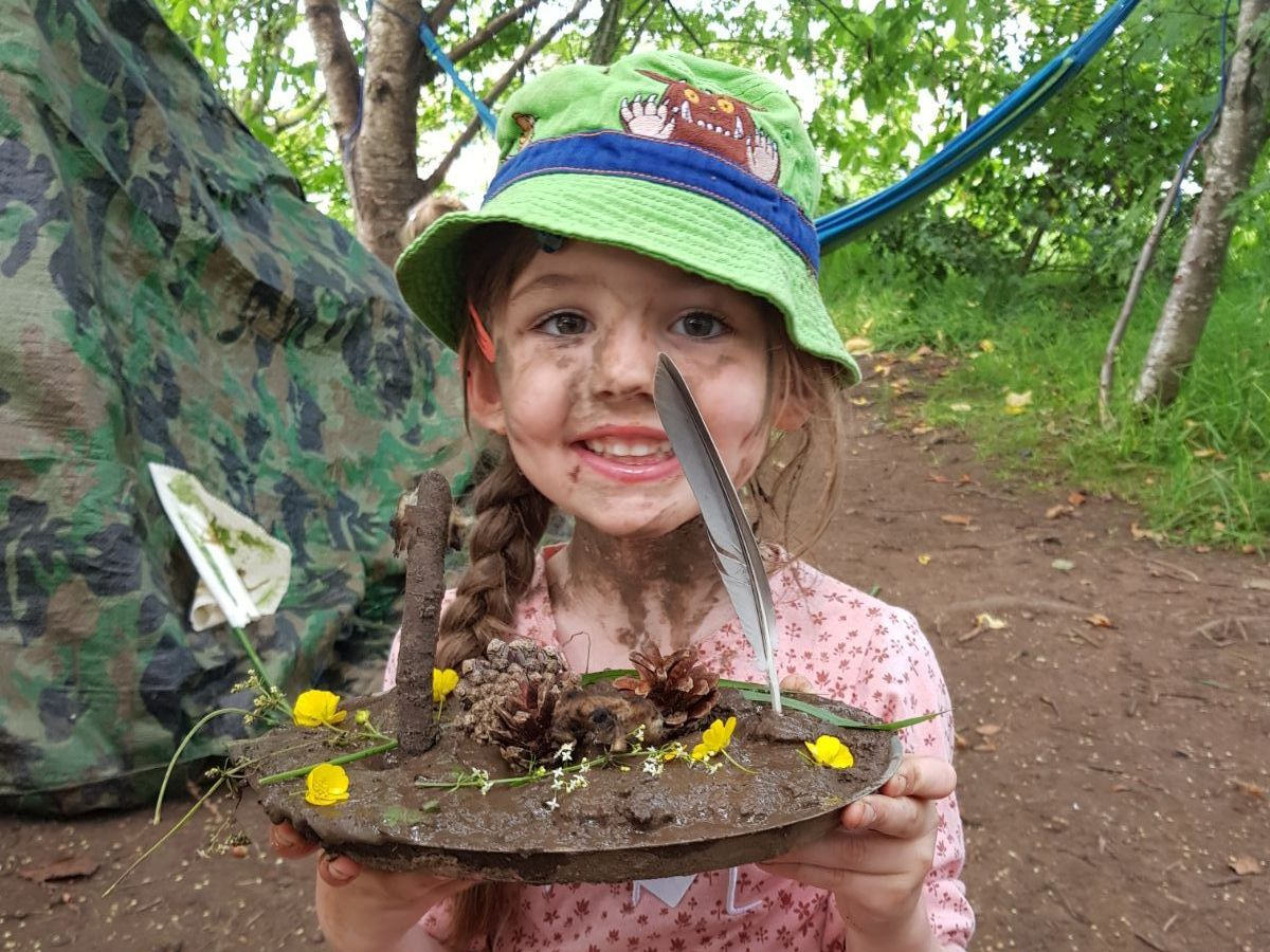 girl in a flowery dress and green hat carrying a plate full of mud and feathers and flowers
