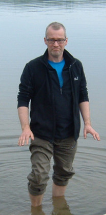 a man with glasses in a black fleece and khaki trousers, standing in water, with his trouser legs rolled up
