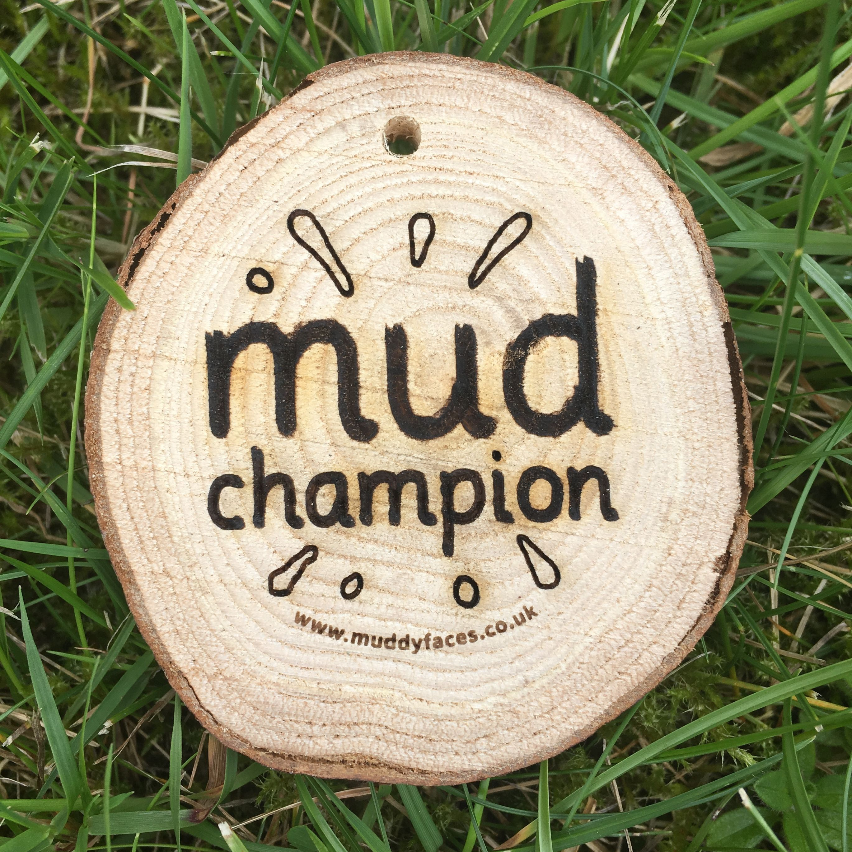 wooden disc with the words Mud Champion burnt into it