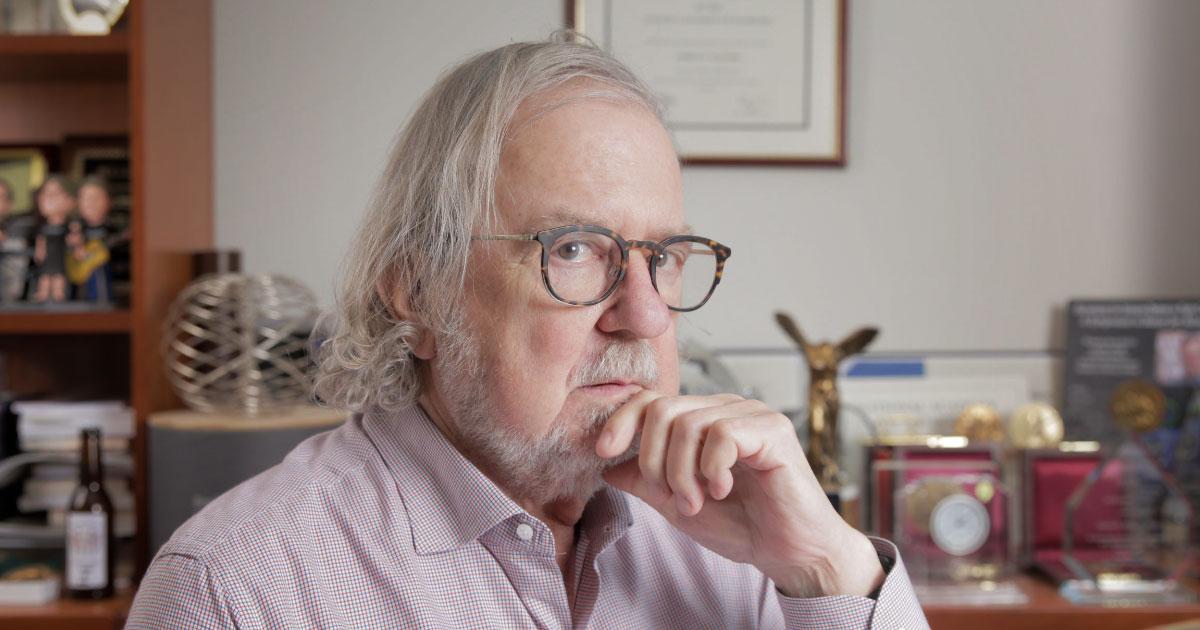 James P. Allison sits at his office desk.