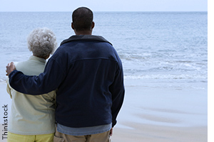 Man with his arm around older woman, looking at the sea