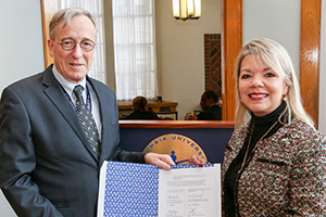 Deans Christian S. Stohler and Ana N. López Fuentes holding a memorandum of understanding
