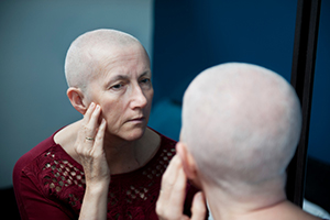 Woman with cancer looking in mirror (kirstyokeeffe/iStock/Getty Images)