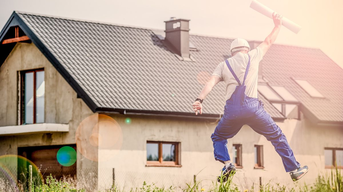 Builder holding plan jumps in the air before a house.