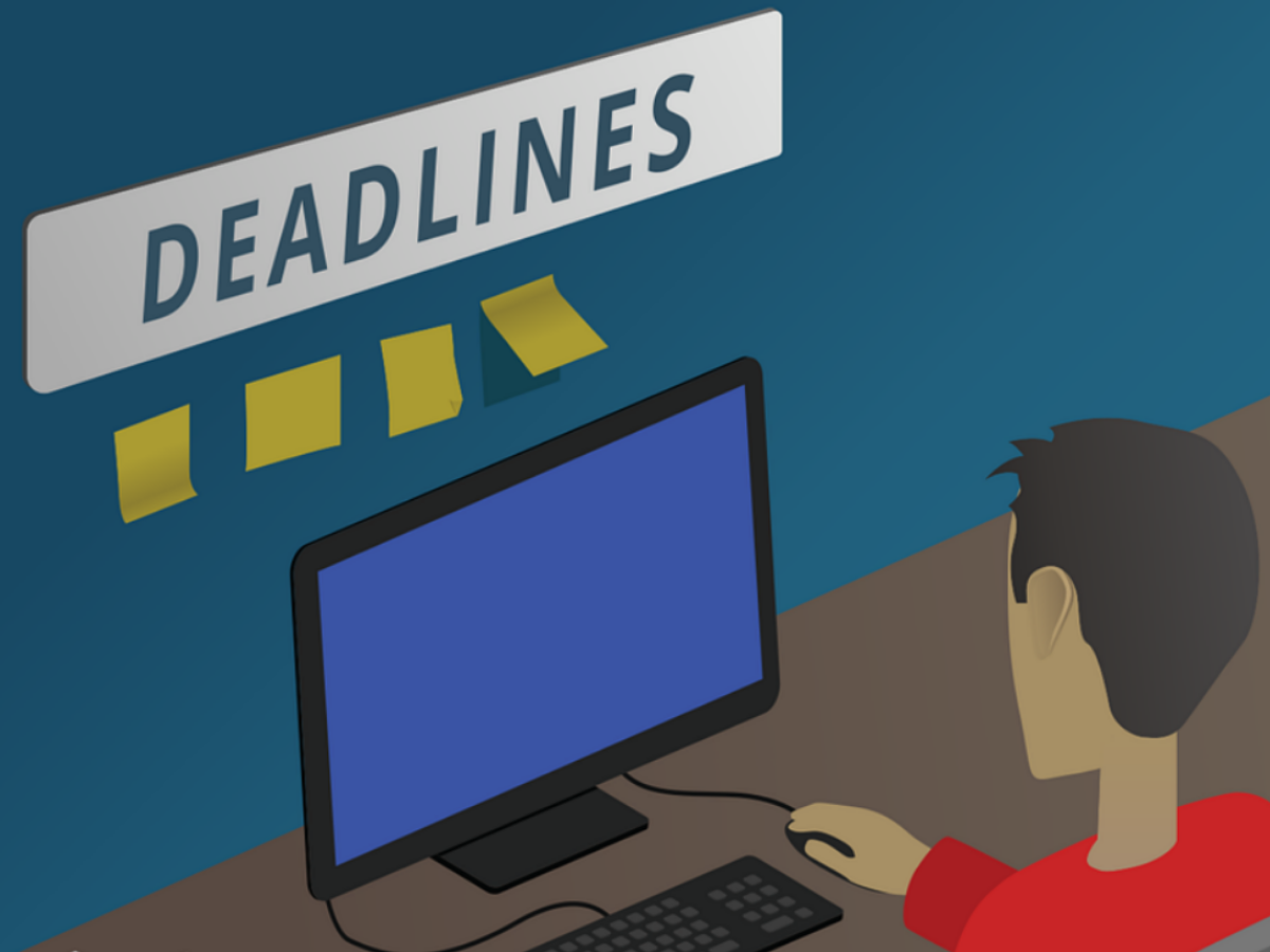 Man at a computer with sign on wall showing deadlines.