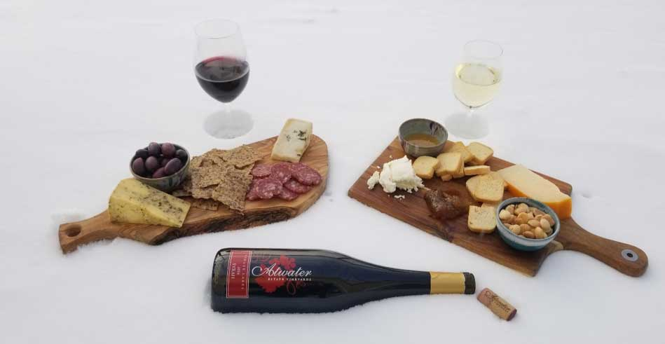 Charcuterie board aside a glass of wine sitting in the snow.